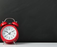 Red alarm clock on black background, with copy space